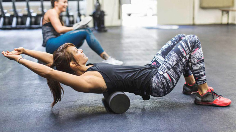 woman using foam roller on upper back