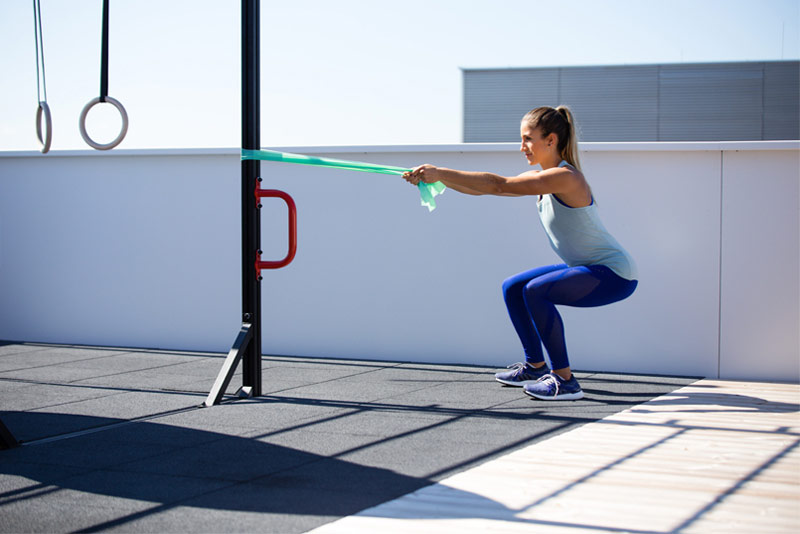 woman performing whole body resistance bands workout