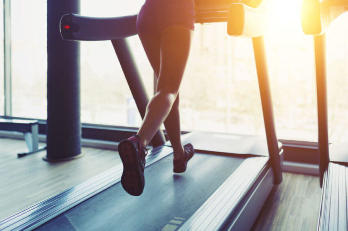 woman running on a treadmill as part of a HIIT workout