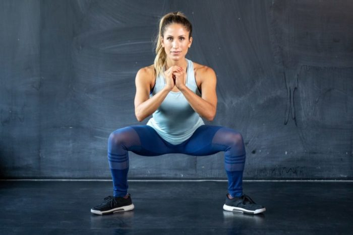 Woman about to do a jumping squat ina HIIT workout plan