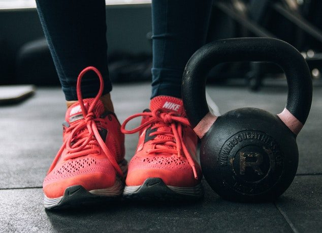 woman standing next to kettlebell ahead of a HIIT workout plan