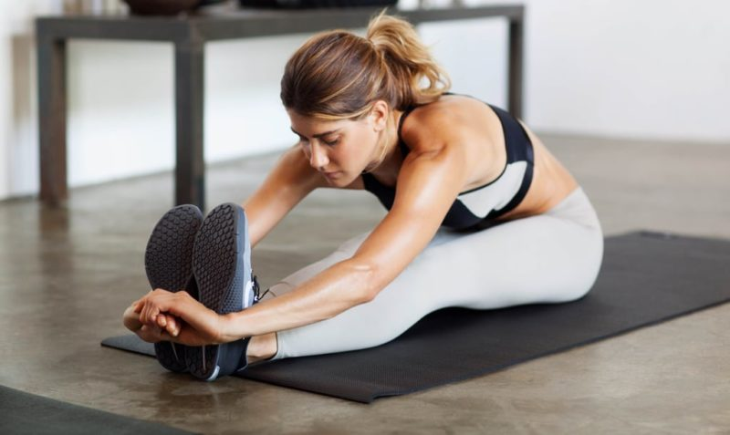 woman stretching at home before a workout