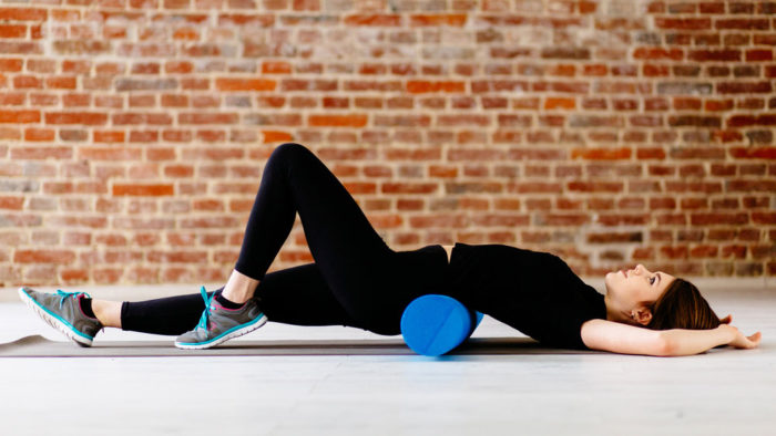Woman recovering from beginner powerlifting program with foam roller