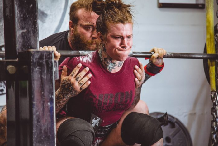 woman at the bottom of a squat on a beginner powerlifting program