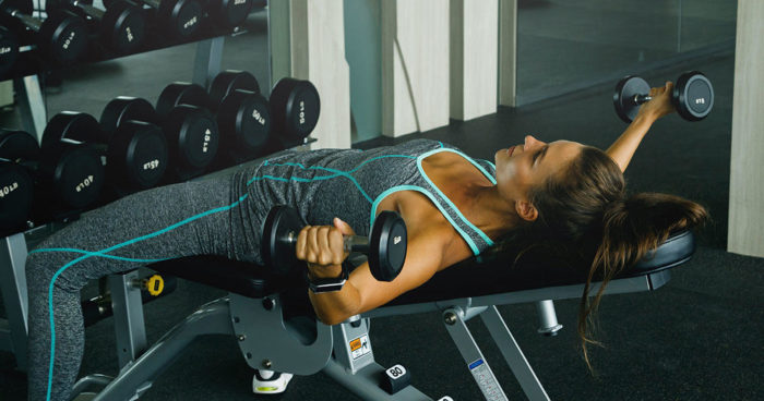 woman doing chest and arms workout with dumbbell flye exercise