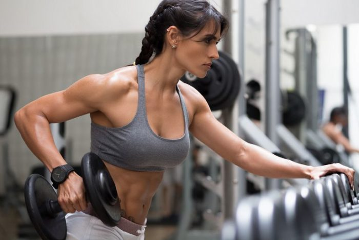 woman doing a chest and arms workout holding a dumbbell