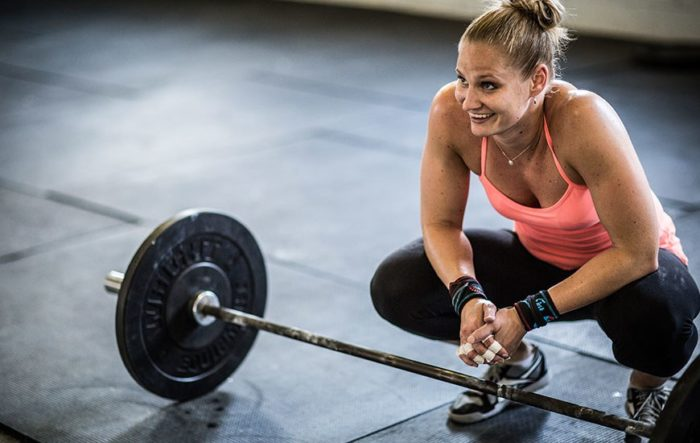 woman smiling with a barbell