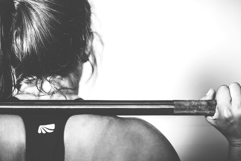 Woman holding a barbell across her back ready to squat as a muscle building exercise.