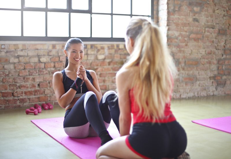 Two women performing sit-ups as part of a strength training without weights routine