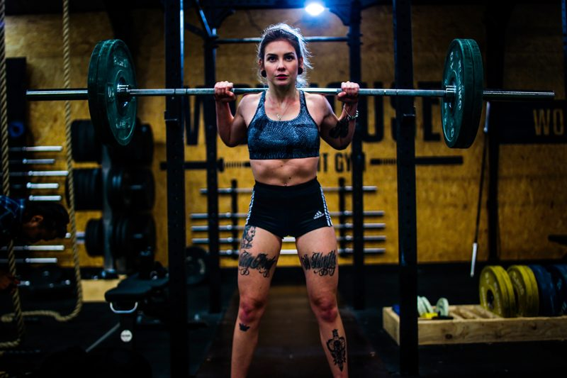 Strong female vegan athlete building muscle by using barbell and following vegan muscle building diet plan