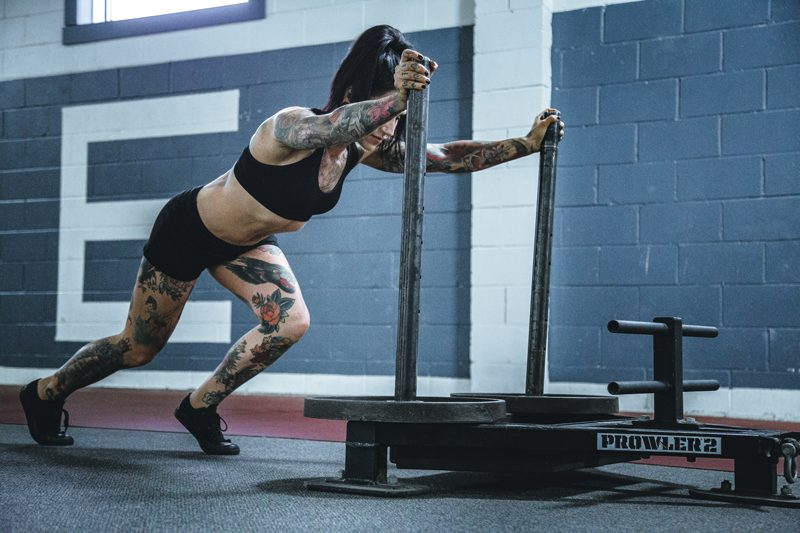 Woman pushing prowler to build muscle